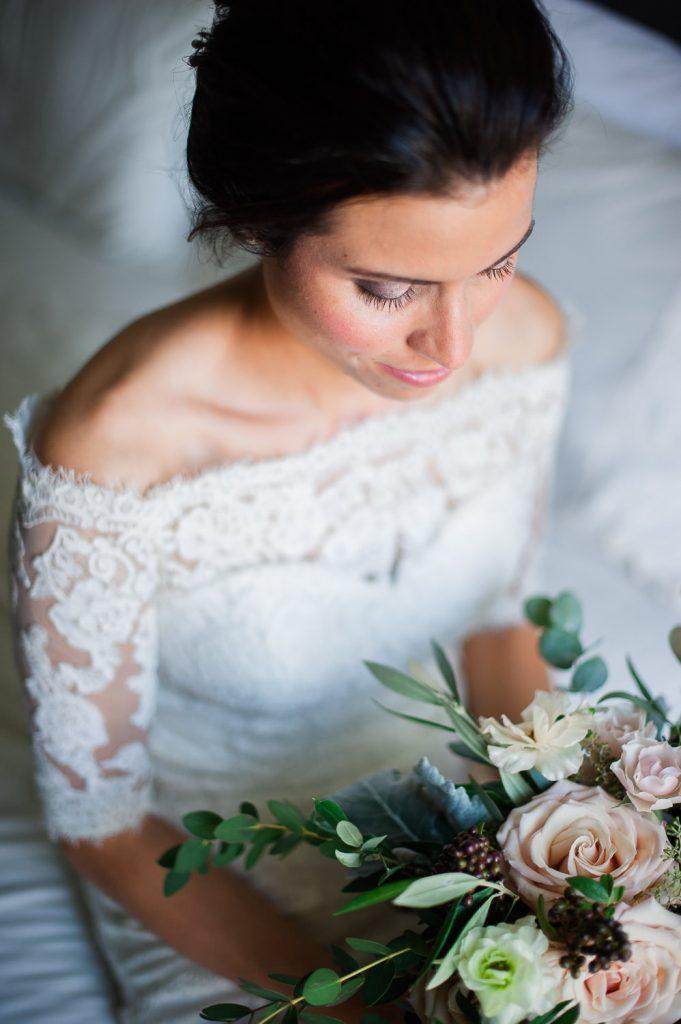mariee dans sa robe en dentelle assise sur un lit tenant un bouquet de fleurs