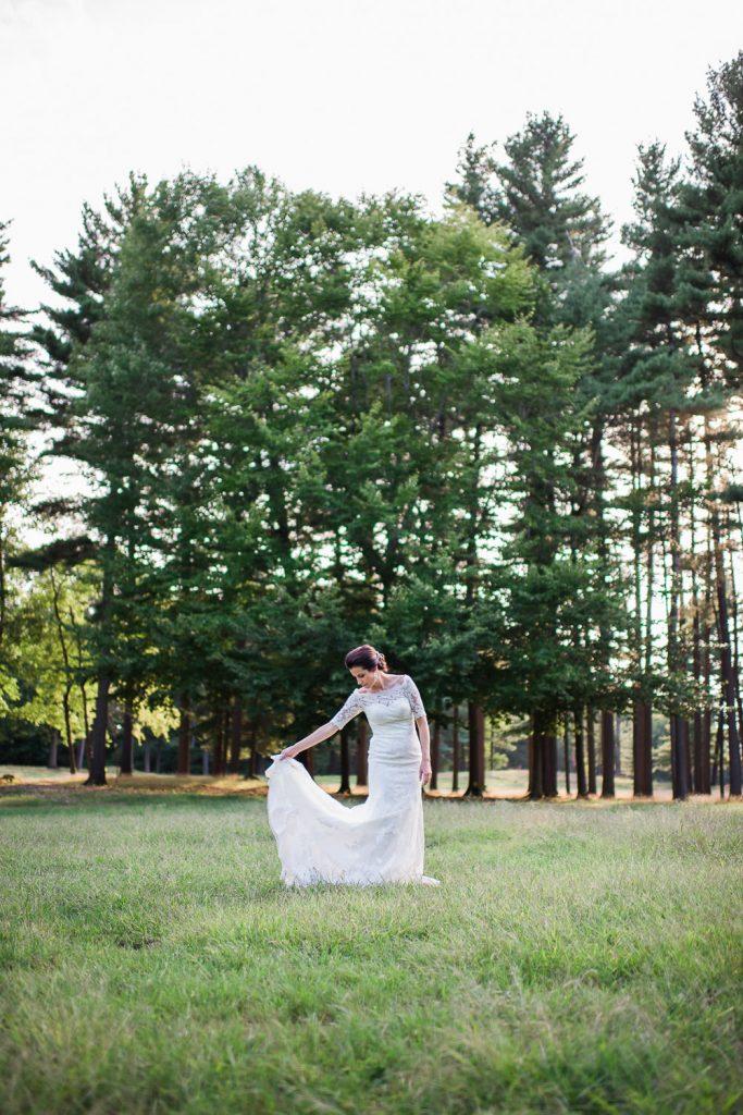Mariee tenant sa robe en dentelle dans un prés au soleil couchant