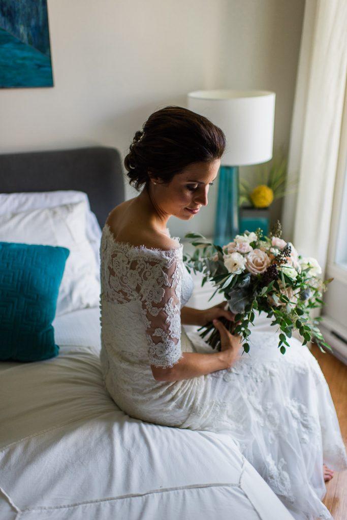 mariee assise dans sa robe en dentelle sur un lit tenant un bouquet de fleurs