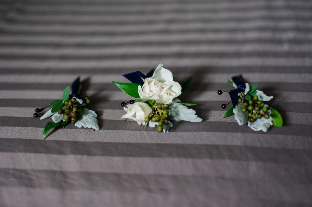 boutonniere sur un lit du marie et des garcons d honneur roses blanches