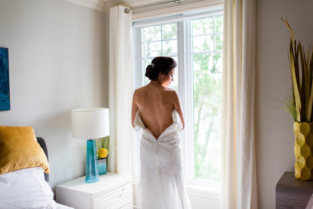 mariee tenant sa robe en dentelle dos dans sa chambre bride holding her weddding dress