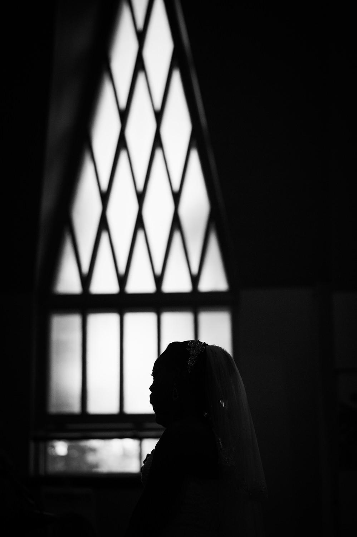le-visage-de-la-mariee-en-contre-jour-avec-la-fenetre-de-la-chapelle-en-arriere-plan-lors-de-la-ceremonie-du-mariage-a-l-eglise-noir-et-blanc