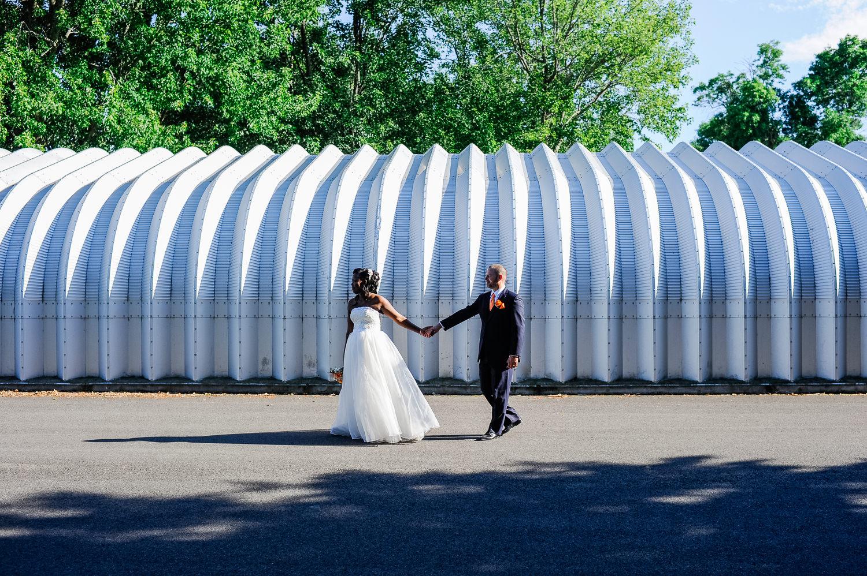 portrait-de-couple-la-mariee-qui-tient-la-main-au-marie-devant-un-hangar-de-tole