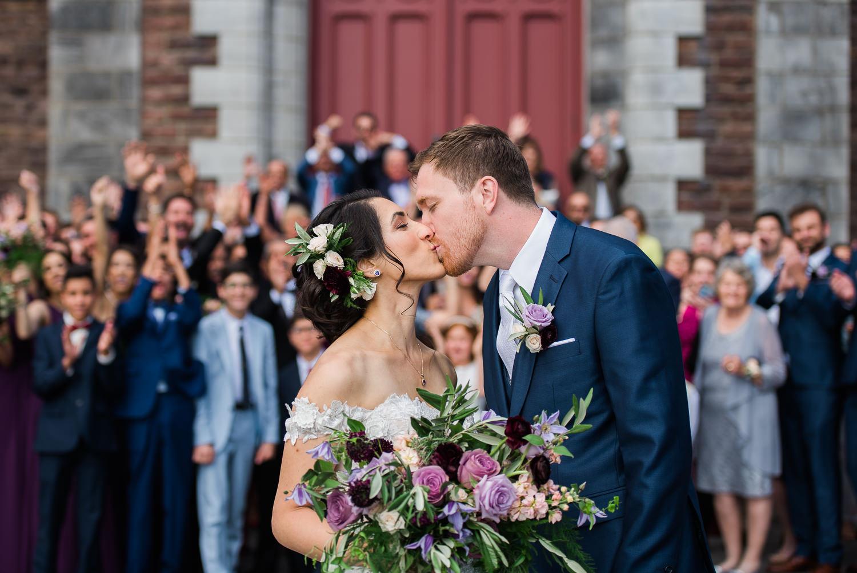 Les-maries-s-embrassent-devant-l-eglise-les-invites-applaudissent-derriere