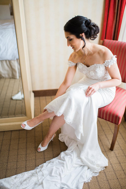 la-mariee-est-assisse-sur-une-chaise-dans-sac-chambre-d-hotel-et-enfile-ses-souliers-pres-de-la-fenetre