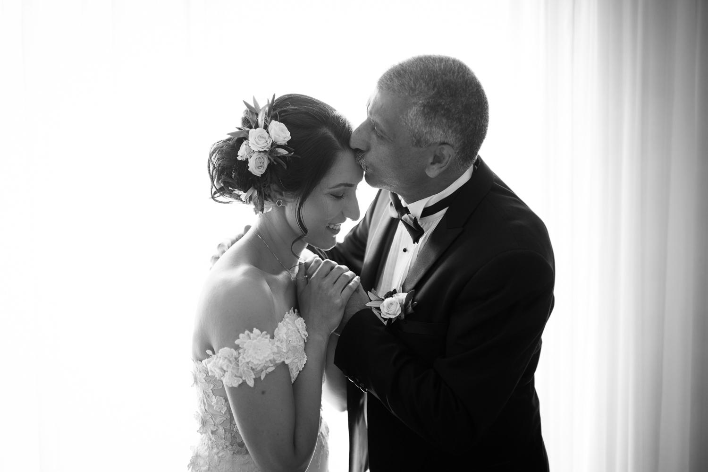 portrait-noir-et-blanc-la-mariee-et-son-pere-se-tiennent-les-mains-en-souriant-devant-la-fenetre-pere-embrasse-sa-fille-dans-le-front