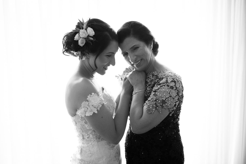 portrait-noir-et-blanc-la-mariee-et-sa-mere-se-tiennent-les-mains-en-souriant-devant-la-fenetre