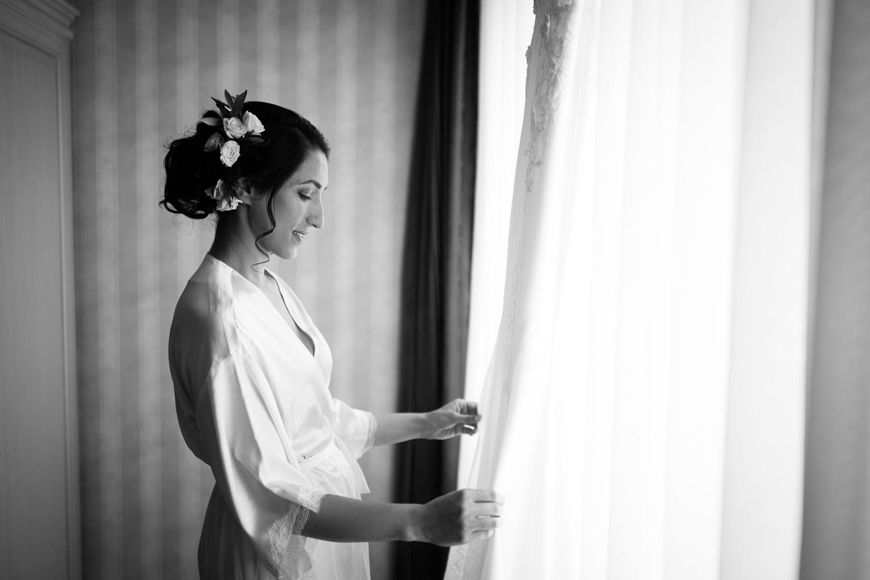La-mariee-en-peignoir-qui-regarde-sa-robe-accrochee-a-la-fenetre-image-en-noir-et-blanc