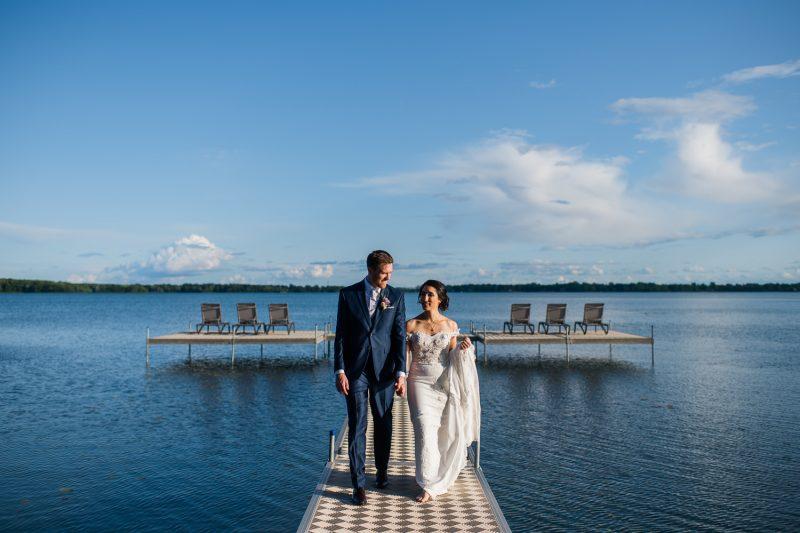portrait-des-maries-qui-marchent-se-tenant-la-main-sur-un-quai-paysage-lac-ciel-bleu-