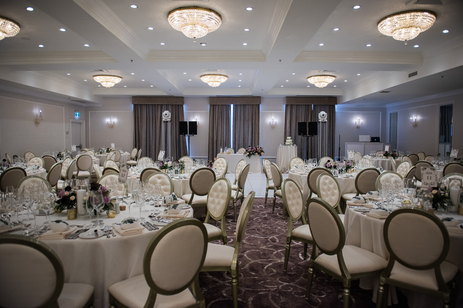 decoration-table-ronde-chaises-cremes-nappes-blanches-chandelier-salle-blanche