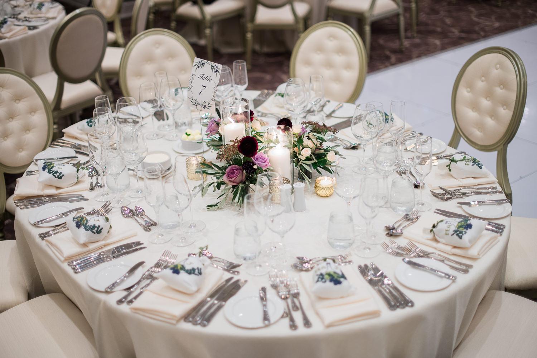 numero-de-table-dessin-olives-feuilles-Table-ronde-centre-de-table-aux-couleurs-aubergine-et-lavande-fleurs-nappe-blanche-chandelles