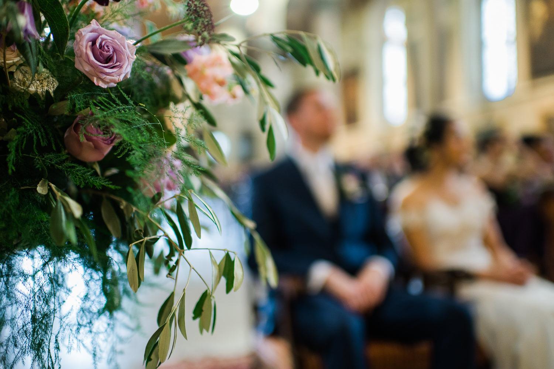 bouquet-de-fleurs-lors-de-la-ceremonie-maries-hors-focus-ecoutant-la-celebration