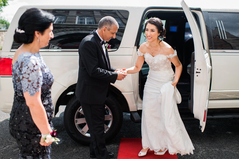 pere-qui-tient-la-ma-de-sa-fille-lorsqu-elle-descend-de-la-limousine-la-mariee-souriante-regarde-sa-mere
