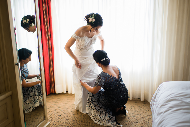 mere-de-la-mariee-aide-sa-fille-a-ajuster-sa-robe-devant-la-fenetre-de-la-chambre-d'hotel