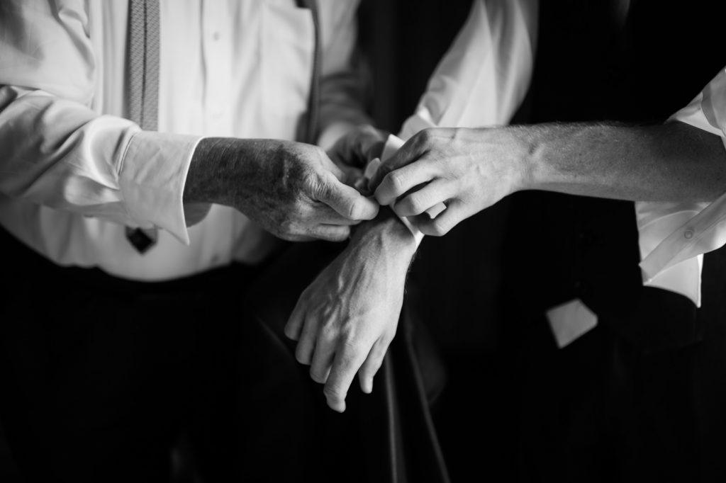Papa-qui-aide-son-fils-à-attacher-bouton-de-manchette-noir-et-blanc