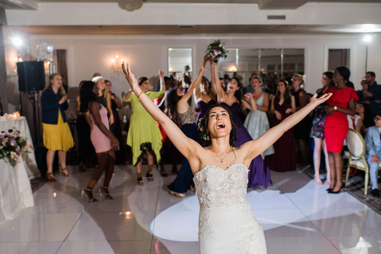 La-mariee-lance-son-bouquet-aux-invites-les-bras-dans-les-airs-salle-de-reception
