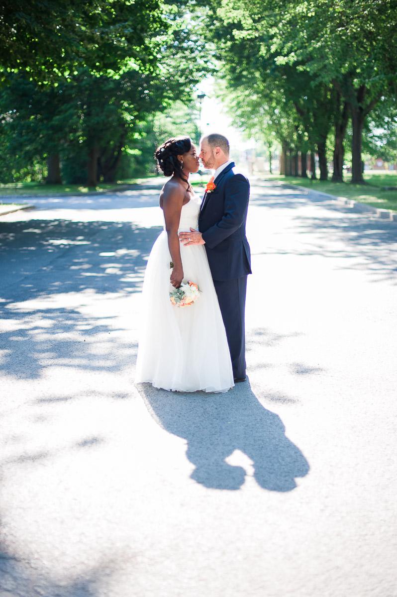 maries au centre de la rue avec leur ombre sur le sol et les arbres en arriere-plan mariage