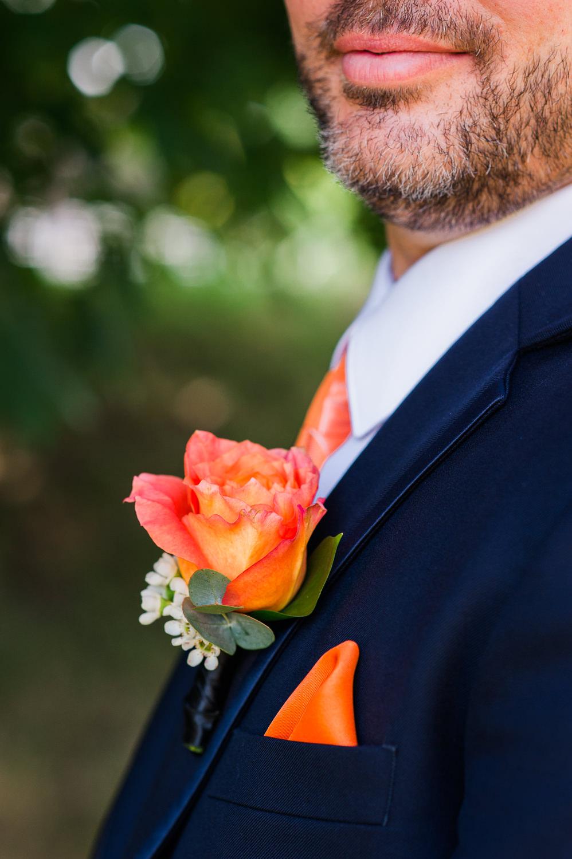 plan-rapproche-de-la-boutonniere-du-marie-une-rose-orange-bas-du-visage