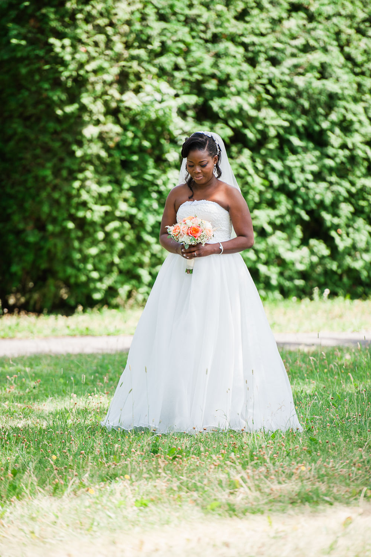 portrait-plein-pied-de-la-mariee-dans-un-parc-elle-regarde-son-bouquet
