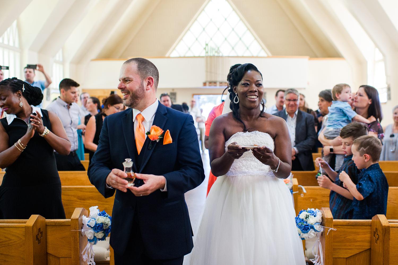 couple-souriant-qui-marche-avec-le-vin-et-le-pain-pourla-celebration-de-l-eucharistie-lors-de-la-ceremonie-de-mariage-a-l-eglise