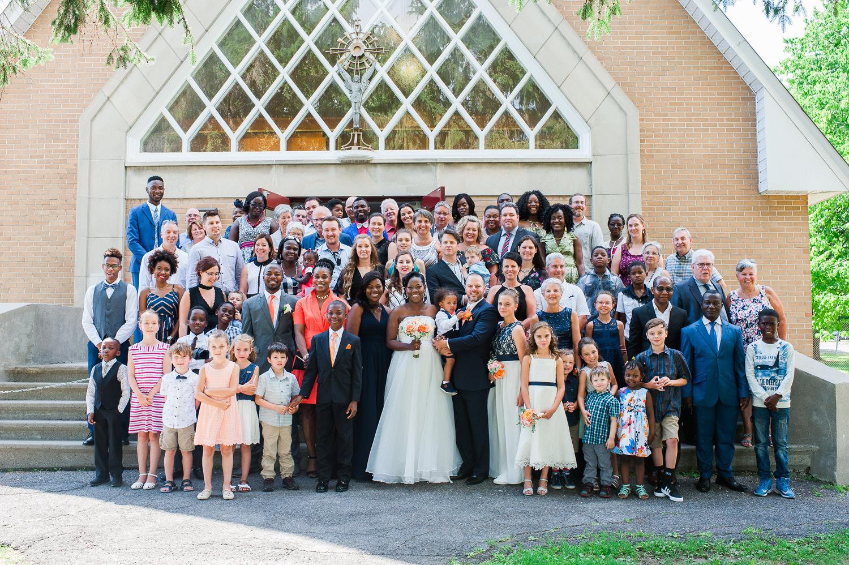 photo-de-groupe-devant-la-chapelle-avec-famille-et-amis-lors-d-un-mariage