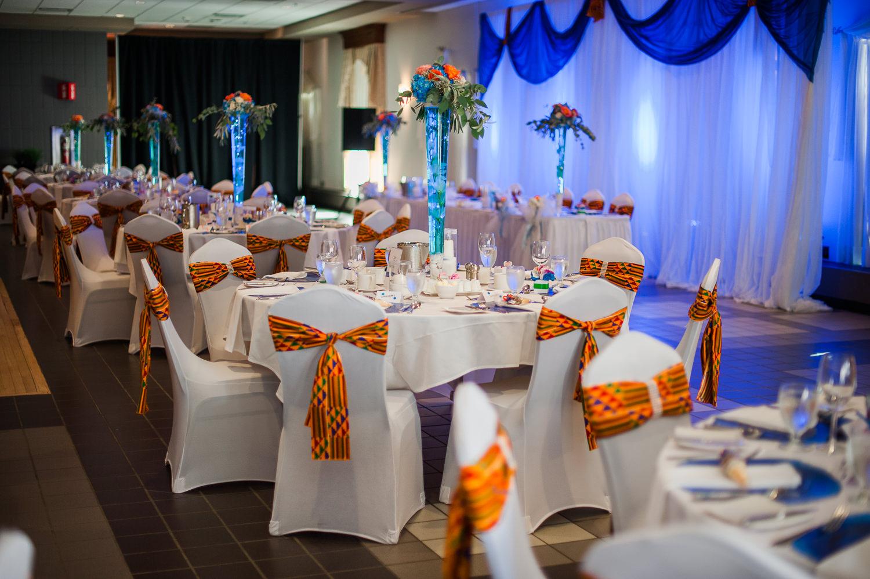 Salle-le-grand-fort-corporation-du-fort-St-Jean-decoration-mariage-table-ronde-nappe-et-couvre-chaise-blanche-decoration-pour-chaise-orangee-centre-de-table-vase-en-verre