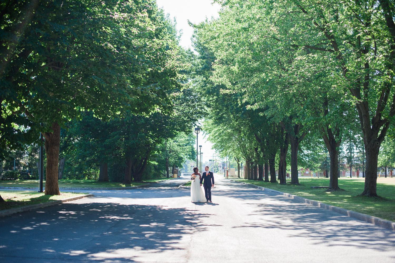 photo-de-couple-mariage-qui-se-tiennent-la-main-en-se-regardant-dans-allee-d-arbres