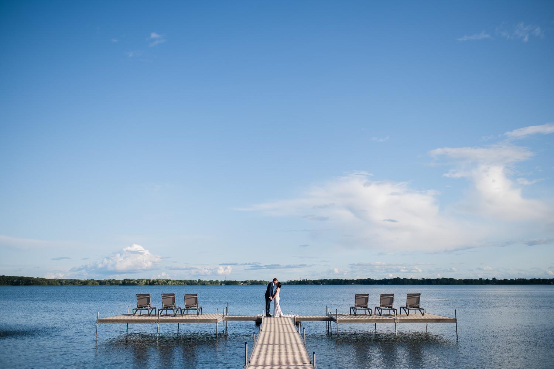 portrait-des-maries-qui-s-embrassent-sur-un-quai-paysage-lac-ciel-bleu